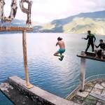 Adrenalinejunkies duiken vanaf een verlaten hotel de zee in