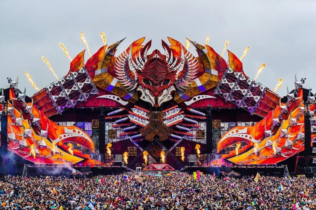 Monsterlijk podium waar vuur uit wordt gespuwd en een grote massa van mensen die staat te dansen