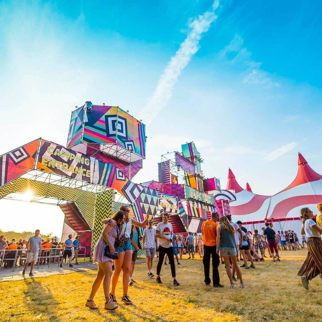 Dansende en lachende mensen staan voor kleurrijke tent van festival Lowlands