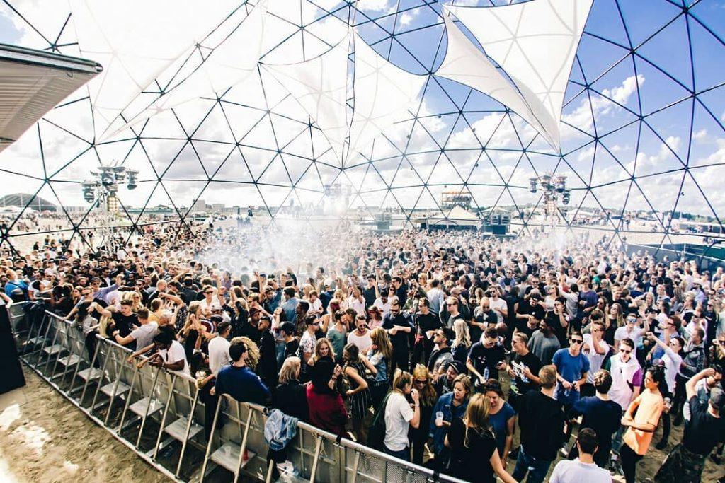 Mensen staan te dansen in een enorme doorzichte bubbel