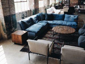 zitplek, blauwe bank, onafgewerkte mumren, ronde houten tafeltje, witte zitstoelen